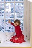 Girl sitting by window decorated with snowflakes