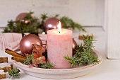 Candle, juniper, Christmas baubles & hydrangea flowers on plate