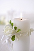 Burning candle with white rose