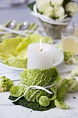 Winter table decoration: candle, savoy cabbage, Brussels sprouts