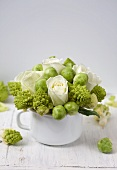 Arrangement of white roses, romanesco and Brussels sprouts