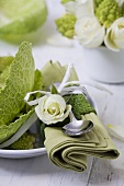 Place-setting with white rose and savoy cabbage leaves