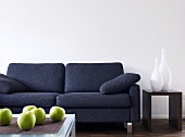 Grey sofa, side table with vases, green apples on table