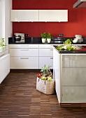 Einkaufstasche in moderner Küche mit weissen Schränken & rot gestrichenen Wänden