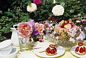 Strawberry tarts and cake in garden with fresh flowers