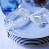 A pile of blue plates tied together with ribbon