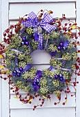 Weihnachtskranz mit violettem Schmuck an weißem Fensterladen