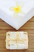 Frangipani flower on towels and a bar of olive soap