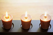 Three burning candles in shallow candle holder