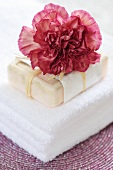 Towel, soap and a carnation (Dianthus caryophyllus)