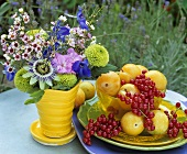 Yellow plums, redcurrants and vase of flowers