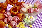 Tulips and coloured sugar eggs on checked tablecloth