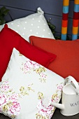 Decorative cushions and small watering can