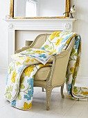 Flowery bedspread and cushion on upholstered chair by fireplace
