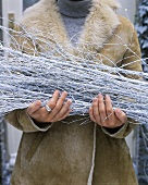 Woman holding white branches (Christmas decorations) outside house