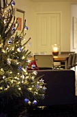 Decorated Christmas tree, dining table in background