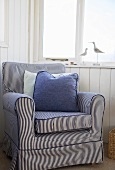 Blue striped chair in a room with a nautical theme