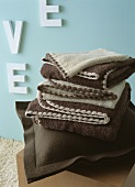Brown felt cushion and brown and beige blankets in front of blue wall with white letters