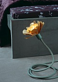 Flower-shaped table lamp with adjustable base at foot of bed