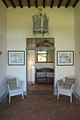 Country style foyer with white wicker chairs and a view through a door opening onto a floor lamp and bench