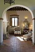 View through an archway on light colored upholstered furniture and tile floor of a country home