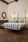 Iron bedstead with white bed linen in a Mediterranean country home