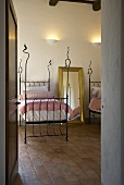 View through an open door into a bedroom with a single bed with a iron bedstead on a tile floor