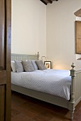 Double bed with a bright green wooden bed stead in a bedroom (country style)