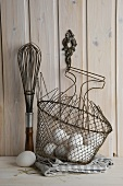 Eggs in a wire basket with a whisk
