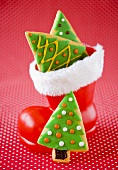 Christmas cookies shaped like Christmas trees, some in a Santa boot