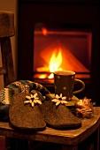 Filzpantoffeln, Lebkuchen und Kakao auf Stuhl vor Kaminfeuer