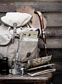 Backpack with walking stick, binoculars, flask and map on a wooden stool