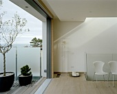 A modern living room with an open terrace door and a view of a terrace with wooden floorboards and potted plants