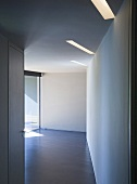 A view along a corridor into an empty room with strip ceiling lighting
