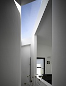 A view through a window-like opening in an anteroom and a skylight in a newly built house