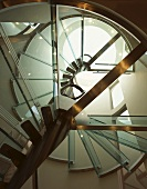 The underneath a spiral staircase with glass stairs and a steel frame