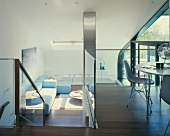 A cool, modern house with a dining area on a mezzanine floor and a view of a sofa in the living room