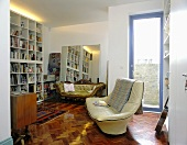 A living room with herring-bone parquet and a white leather sofa in front of terrace door and bookshelves with indirect lighting