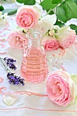 Rose oil, pink roses and lavender flowers