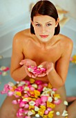 Young woman in a rose petal bath