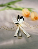 One Set of Silverware tied with Ribbon on Table Cloth with Tulips in Rear