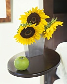 Still life with sunflowers and a green apple