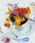 Sommer-Blumenstrauss in einer Vase auf einem Teller