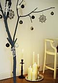Weihnachtlich dekorierter Ast neben Silbertablett mit Kerzen