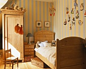 A childrens' room with wooden furniture and stripped wallpaper
