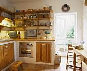Gemauerte Küchenzeile im ländlichen Stil mit Holztüren, einem Küchenregal ums Eck und Bodenfliesen