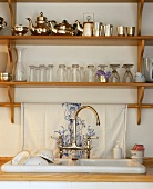 A sink with a wooden shelf filled with glasses and silverware