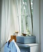 Kästchen mit Bürste & Kette am Fenster in einem Schlafzimmer