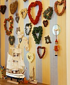 Various wreaths on the wall with a model sail boat