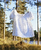 A girl's dress hanging on a washing line